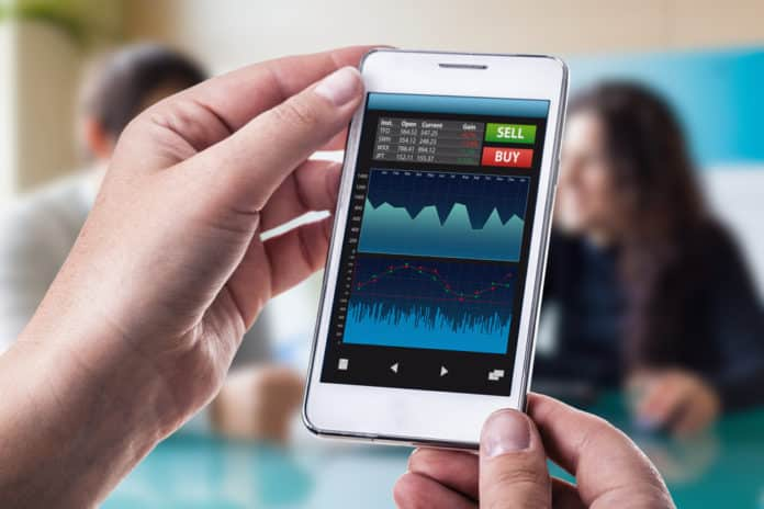 A woman holding a smart phone running a trading or forex app with charts and data. Dario Lo Presti / Shutterstock.,com