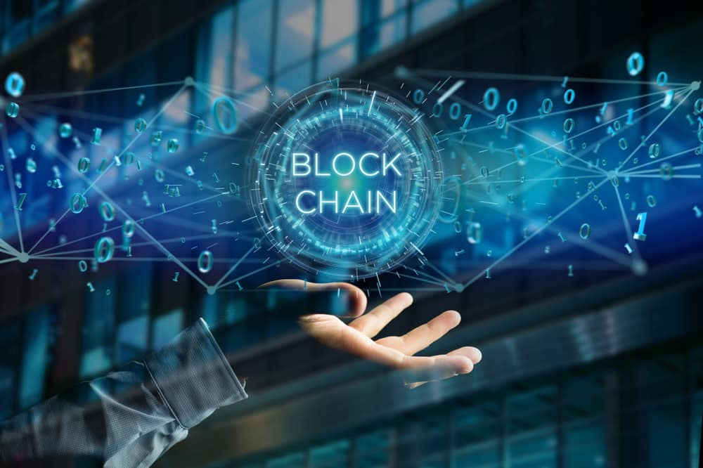 View of a Blockchain title with 0 and 1 data flying over. Production Perig / Shutterstock.com