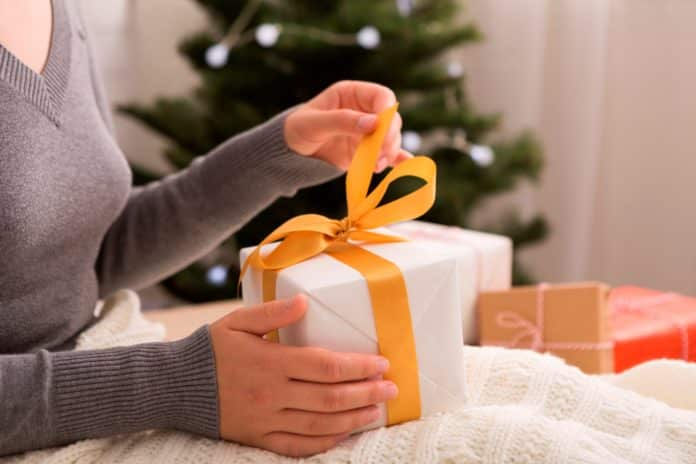 Unpacking presents. Woman opening gift box on Christmas background